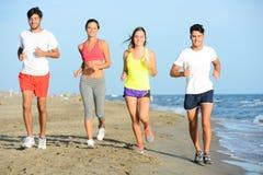 Le groupe des jeunes courant dans le sable sur le rivage d'une plage par la mer au coucher du soleil pendant des vacances d'été e Photos libres de droits