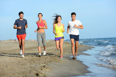 Le groupe des jeunes courant dans le sable sur le rivage d'une plage par la mer au coucher du soleil pendant des vacances d'été e Photographie stock