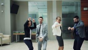 Le groupe des jeunes enthousiastes danse dans le hall du centre moderne d'affaires appréciant la partie d'entreprise et ayant l'a clips vidéos