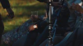 Le groupe des jeunes fume le narguilé et a des boissons dehors un jour d'été clips vidéos