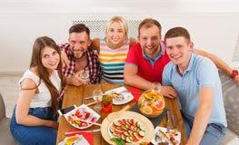 Le groupe des jeunes heureux à la table de dîner, amies font la fête Images libres de droits