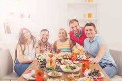 Le groupe des jeunes heureux à la table de dîner, amies font la fête Photo stock