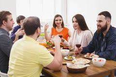 Le groupe des jeunes heureux à la table de dîner, amies font la fête Images stock