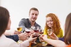 Le groupe des jeunes heureux à la table de dîner, amies font la fête Image libre de droits