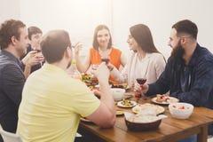 Le groupe des jeunes heureux à la table de dîner, amies font la fête Photographie stock