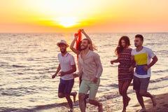 Le groupe des jeunes heureux court sur le fond de la plage et de la mer de coucher du soleil Photographie stock libre de droits