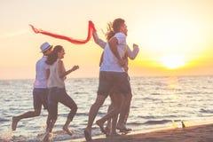 Le groupe des jeunes heureux court sur le fond de la plage et de la mer de coucher du soleil Images stock