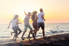 Le groupe des jeunes heureux court sur le fond de la plage et de la mer de coucher du soleil Photo libre de droits