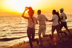 Le groupe des jeunes heureux court sur le fond de la plage et de la mer de coucher du soleil Image libre de droits