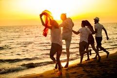 Le groupe des jeunes heureux court sur le fond de la plage et de la mer de coucher du soleil Photos stock