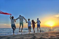 Le groupe des jeunes heureux court sur le fond de la plage et de la mer de coucher du soleil Images libres de droits