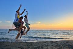Le groupe des jeunes heureux court sur le fond de la plage et de la mer de coucher du soleil Photos libres de droits