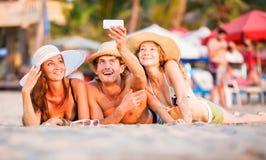 Le groupe des jeunes heureux se trouvant sur le wite échouent Photos stock