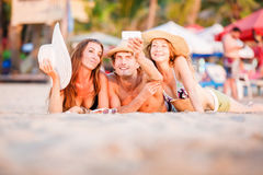 Le groupe des jeunes heureux se trouvant sur le wite échouent Photographie stock libre de droits