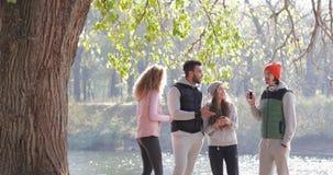 Le groupe des jeunes parlent le lever de soleil extérieur de téléphone intelligent de prise, matin Autumn Park Near Tree de commu banque de vidéos