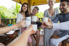 Le groupe des jeunes prenant le petit déjeuner sur l'hôtel tropical de terrasse, tintement d'amis met en forme de tasse des vacan Images libres de droits
