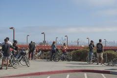 Le groupe des jeunes se ferment avec des bicyclettes observant au centre ville Les gens parlant avec des gratte-ciel sur le fond photos libres de droits