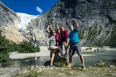 Le groupe des jeunes se tenant sur la pierre prend une photo Photographie stock libre de droits