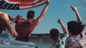 Le groupe des jeunes soulèvent le drapeau américain Image stock