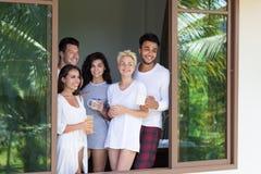 Le groupe des jeunes sur l'hôtel tropical de terrasse, amis de matin apprécient des vacances tropicales de vacances de vue Photographie stock libre de droits