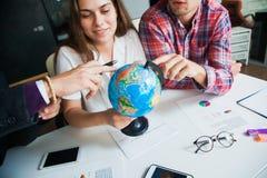Le groupe des trois jeunes avec le globe choisissent le pays pour voyager à Photo stock