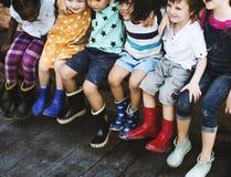 Le groupe du jardin d'enfants badine des amis arment autour de se reposer et de smilin Photo libre de droits