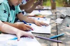 Le groupe du jardin d'enfants badine des amis dessinant la classe d'art dehors Image stock