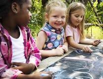 Le groupe du jardin d'enfants badine des amis dessinant la classe d'art dehors Photos stock