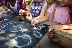 Le groupe du jardin d'enfants badine des amis dessinant la classe d'art dehors Photographie stock
