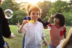 Le groupe du jardin d'enfants badine des amis jouant l'amusement de soufflement de bulles Images stock