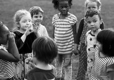 Le groupe du jardin d'enfants badine des amis tenant des mains jouant au parc Photo stock