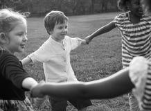 Le groupe du jardin d'enfants badine des amis tenant des mains jouant au parc Photo libre de droits