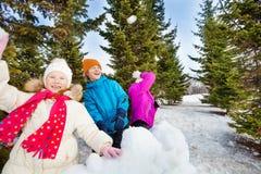 Le groupe du jet heureux d'enfants lance des boules de neige pendant le combat Photographie stock libre de droits