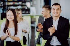 Le groupe ethnique multi d'affaires salue quelqu'un avec l'applaudissement et le sourire à la conférence images stock