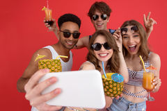 Le groupe gai d'amis buvant des cocktails font le selfie par phone Photo stock