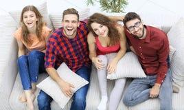 Le groupe gai d'amis rient, se reposant sur le divan Photographie stock