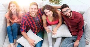 Le groupe gai d'amis rient, se reposant sur le divan Photos libres de droits