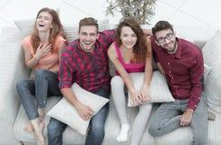 Le groupe gai d'amis rient, se reposant sur le divan Image libre de droits