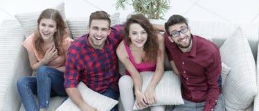 Le groupe gai d'amis rient, se reposant sur le divan Images libres de droits
