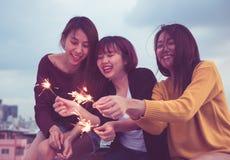 Le groupe heureux de amie de l'Asie apprécient et jouent le cierge magique au toit Photographie stock libre de droits
