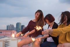 Le groupe heureux de amie de l'Asie apprécient et jouent le cierge magique au toit Images stock