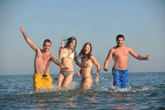 Le groupe heureux de gens ont l'amusement et le fonctionnement sur la plage Images stock
