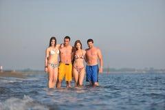 Le groupe heureux de gens ont l'amusement et le fonctionnement sur la plage Photographie stock