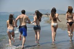 Le groupe heureux de gens ont l'amusement et le fonctionnement sur la plage Images libres de droits