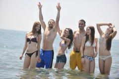 Le groupe heureux de gens ont l'amusement et le fonctionnement sur la plage Image libre de droits