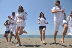 Le groupe heureux de gens ont l'amusement et le fonctionnement sur la plage Photographie stock libre de droits