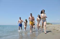 Le groupe heureux de gens ont l'amusement et le fonctionnement sur la plage Photos libres de droits