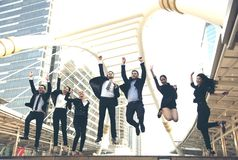 Le groupe heureux de travail d'équipe d'affaires sautent  Célébration de concept photo stock
