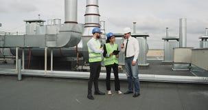Le groupe multi-ethnique de l'architecte de travailleurs et deux ingénieurs ont une conversation sur le dessus de toit du bâtimen banque de vidéos
