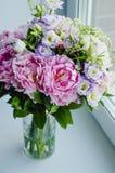 Le groupe riche de pivoines roses pivoine et de roses d'eustoma de lilas fleurit dans le vase en verre sur le fond blanc Style ru Photos stock